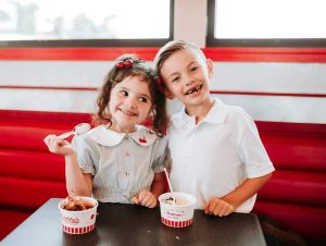 Two young children eating custard