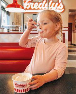 young girl eating frozen custard dish
