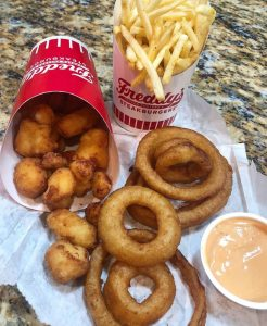 Onion rings, cheese curds and french fries: A delicious tri of Freddy's sides!