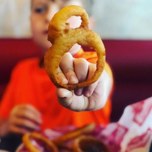 A young FredHead holding up some delicious Freddy's onion rings!
