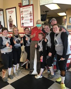 A team of athletic FredHeads posing with a cardboard image of Freddy